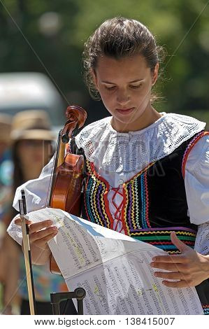 ROMANIA TIMISOARA-JULY 7 2016:Singer at violin from Poland in traditional costume present at the international folk festival