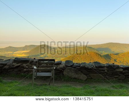 View from hill over rest place with old wooden chair down to countryside. Spring morning on the peak of hill.