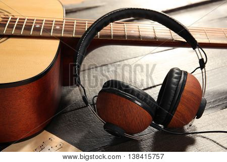 Headphones and guitar on wooden background