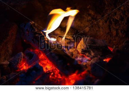 Coals and fire of the campfire in the dark night closeup