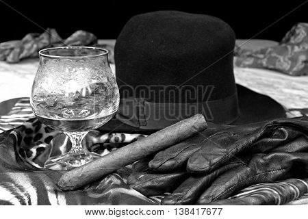 Black hat on a scarf with black leather gloves and a cigar on a marble table in black and white