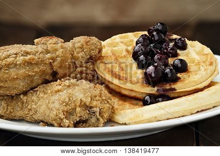 Three pieces of deep fried chicken with waffles served with fresh blueberry sauce. Extreme shallow depth of field.