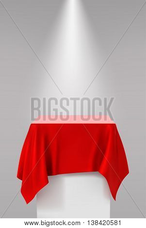 Presentation pedestal covered with a red silk cloth in front of a white wall illuminated by a spot light