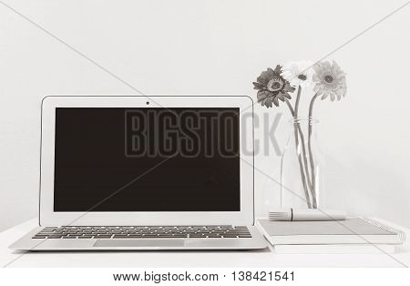 Closeup computer notebook on blurred white wood desk and wallpaper wall in room texture background beautiful work place interior of house concept in black and white tone