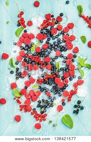 Fresh summer garden berry variety. Rasberry, black and red currant, bilberrry and mint leaves on crushed ice over blue background, top view, vertical composition