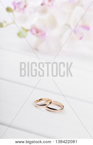 golden wedding rings with flowers on white wooden table