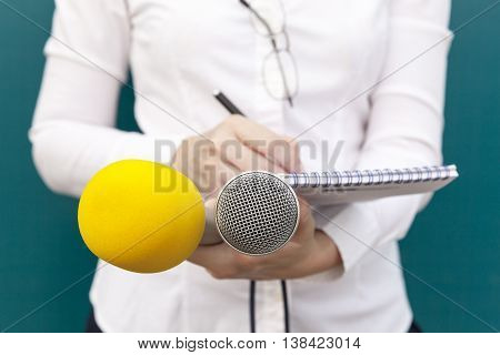 Female reporter or journalist at news conference writing notes and holding microphones