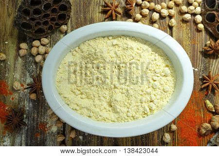 Colorful Indian food ingredients - gram flour chickpea and spices on textured wooden table top