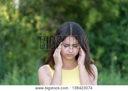 teen girl with migraine outdoors in a summer