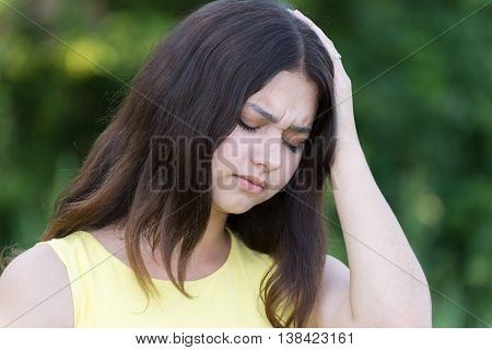 upset teen girl holding a hand behind his head