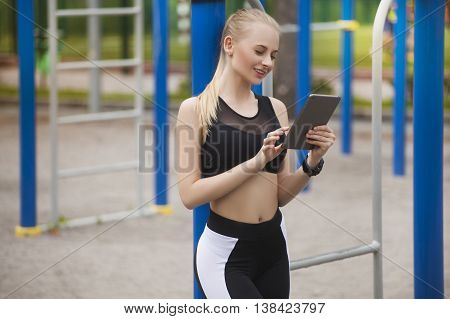 A girl in training looks at the tablet . During a break