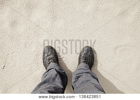 Male Feet In Shoes Stand On White Wet Sand