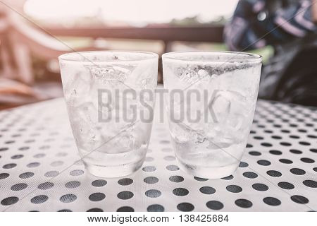 Glasses With Ice Cubes On Black Dot Background Table