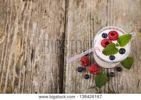 Smoothie with blueberries and raspberries on a wooden table