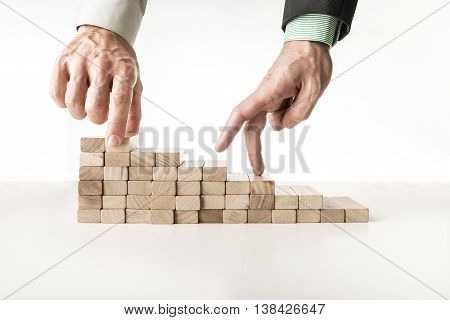 Male hand building steps with wooden pegs for the other one to walk his fingers up towards personal and career growth.