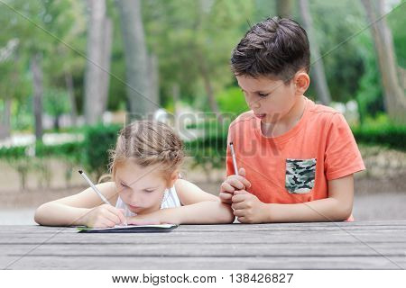 Hapy kids learn in a park. Brother and sister together do the job. Boy and girl sitting at the table and doing exercise.