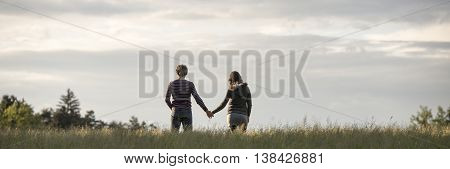 Wide panoramic view on couple holding hands in field from behind below partly cloudy sky with copy space.