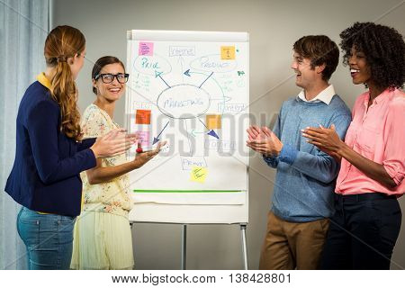 Coworkers discussing on white board in office