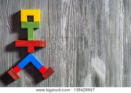 The abstract figure of a walking man of colorful wooden puzzles. Abstract man of Tetris shapes