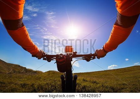 Hands in orange jacket holding handlebar of a bicycle with green meadow on background