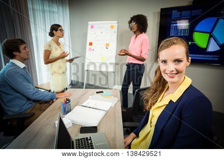 A colleague smiling at camera while coworkers discuss flowchart on whiteboard in the office