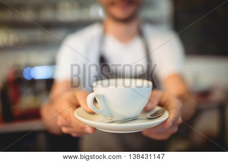 Close-up of male barista serving coffee at cafeteria