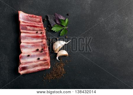 Lamb ribs on the black chalkboard with copy space for your text. The photo could be used to promote lamb pork or beef meat