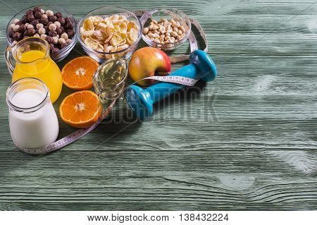 The concept of a healthy lifestyle. Cornflakes orange juice yogurt nuts honey tangerines apple dumbbell and measuring tape on rustic wooden table. Cereals and fruit - diet and breakfast