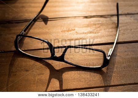 glasses on wooden table with sunlight and shadow selective focused