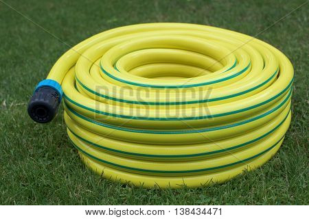 Yellow hose-pipe with couplung on a grass
