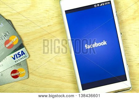 BUNG KAN THAILAND - JANUARY 15 2016: smart phone display facebook app and credit card on office desk selective focused