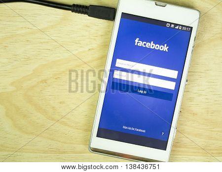 BUNG KAN THAILAND - JANUARY 15 2016: smart phone display facebook app is charging selective focused