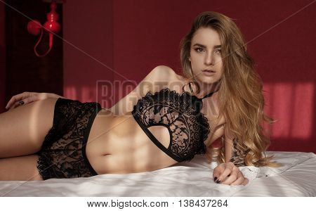Beautiful and sexy brunette young woman wearing black lingerie in bed .Fashion shoot lingerie indoor .Sexy young girl in black lingerie in hotel