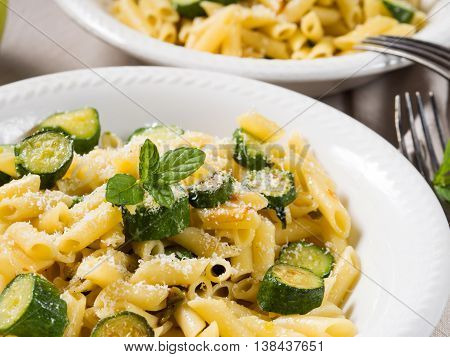 Pennette pasta with courgettes fresh mint and grated parmesan cheese on beige table cloth