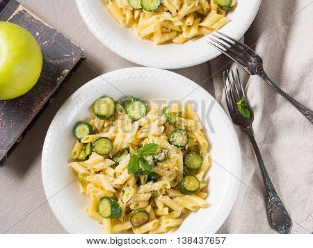 Pennette pasta with courgettes fresh mint and grated parmesan cheese on beige table cloth. Top view