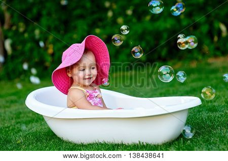 little girl bathes in a bath with soap bubbles.