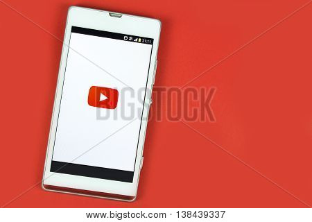 BUNG KAN THAILAND - FEBRUARY 19 2016: smart phone display youtube app on red background space for caption