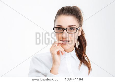 Cute lovely young businesswoman in glasses standing and touching her lips over white background