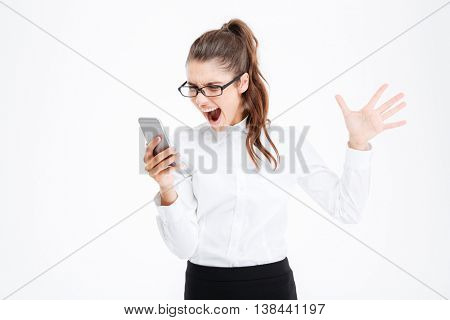 Annoyed hysterical young business woman in glasses talking on cell phone and screaming over white background