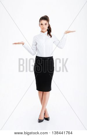 Full length of beautiful young businesswoman standing and holding copyspace on both palms over white background