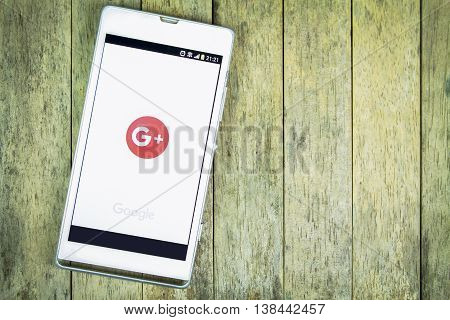 BUNG KAN THAILAND - FEBRUARY 19 2016: smart phone display google plus app on wood background space for caption