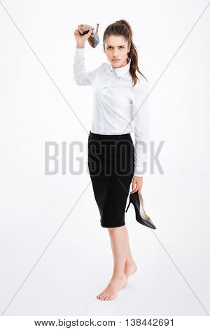 Angry irritated young businesswoman standing and throwing high heels shoes over white background