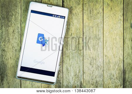 BUNG KAN THAILAND - FEBRUARY 19 2016: smart phone display google translate app on wood background space for caption
