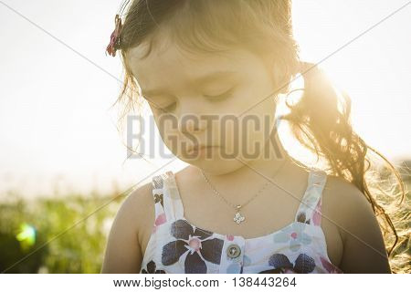 A Portrait of five years old caucasian child girl sunset