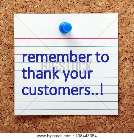 The words Remember to Thank Your Customers in blue text on a note card pinned to a cork notice board as a reminder