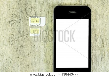 smart phone on wood table with sim card and micro sim card