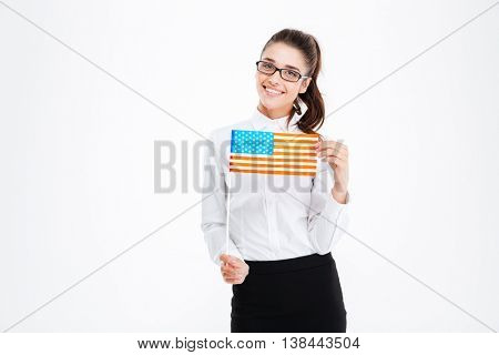 Cheerful attractive young businesswoman in glasses holding USA flag over white background