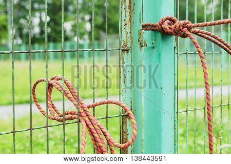 Rope is tied to metal green fence.