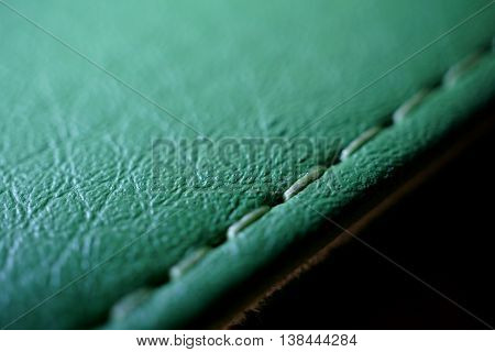 Macro detail of a green thread stitching green stitched leather case