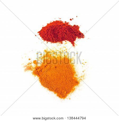 Turmeric (Curcuma) Powder and Pile of red paprika powder isolated on white background